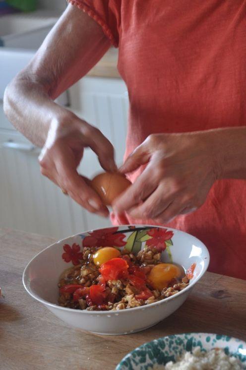 Alle melanzane tritate si aggiungono le uova e dei pomodorini a pezzetti