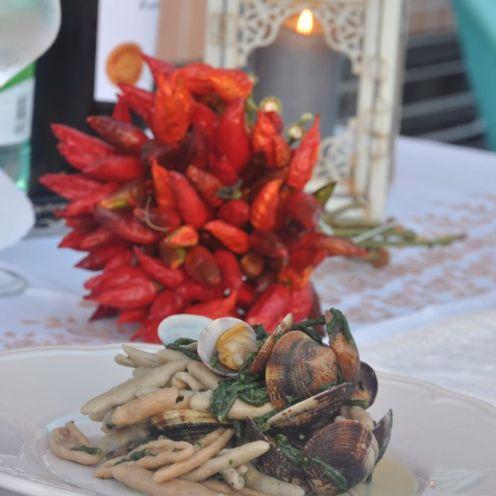 Tutto pronto per la cena, candele, vino bianco e un bel piatto di capunti con vongole veraci e salicornia