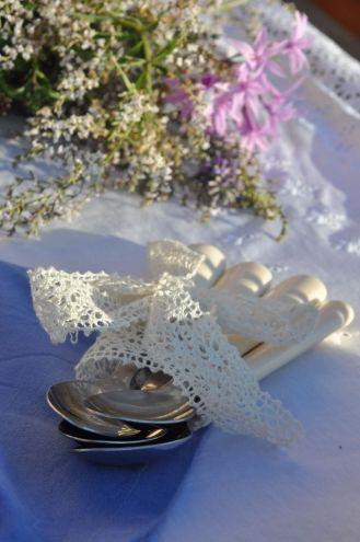 Cucchiaini da servizio avvolti nel pizzo e fiori di erba cedrina